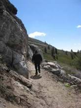 Hiker walks along dirt trail along rocky cliff on one side and rocks into green hills on the other.
