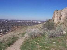 View of Boise from Table Rock with dirt trail, grass and cliff in image.