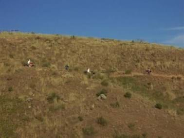 Foothill with ATV riders and others using trail with blue sky.