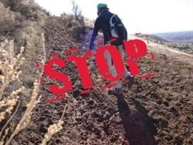 Mountain biker is riding uphill on a muddy trail. The word STOP is written over the image in big red letters.