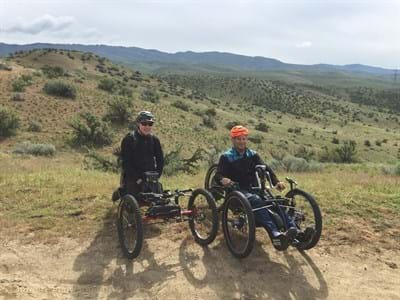 Two adaptive cycle users stopped on a foothills trail overlooking the City of Boise.
