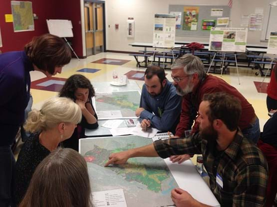 Group of adults sitting around a table looking at map of trail system.