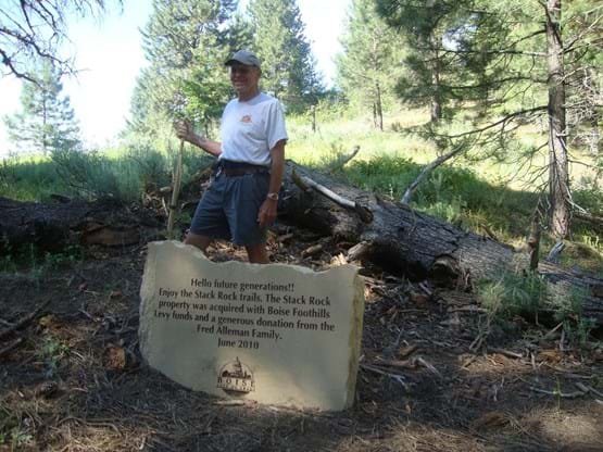 "Hiker poses by a rock that has engraved on it ""Hello future generations!! Enjoy the Stack Rock trails. The Stack Rock property was acquired with Boise Foothills Levy funds and a generous donation from the Fred Alleman Family. June 2010."""