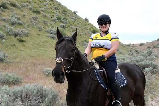 "Woman on horseback with yellow and white jersey that says ""Ranger""."